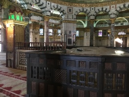 Beneath the dome is the rock. It is the top of the mountain and simply sticks out above the floor level. ~ To the left is the mirbar, where the imam offers a short talk before Friday prayers.